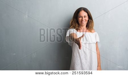 Middle age hispanic woman standing over grey grunge wall smiling friendly offering handshake as greeting and welcoming. Successful business.