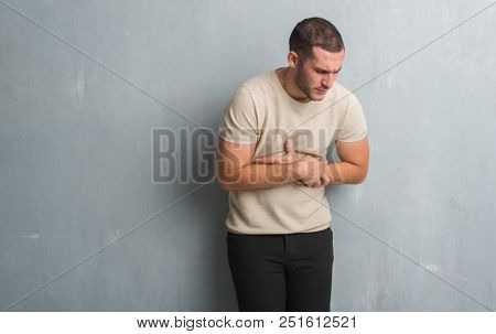 Young caucasian man over grey grunge wall with hand on stomach because nausea, painful disease feeling unwell. Ache concept.