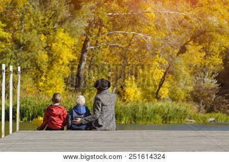 Mom And Two Children Are Sitting On The Pier. Sunny Autumn Day. Back View