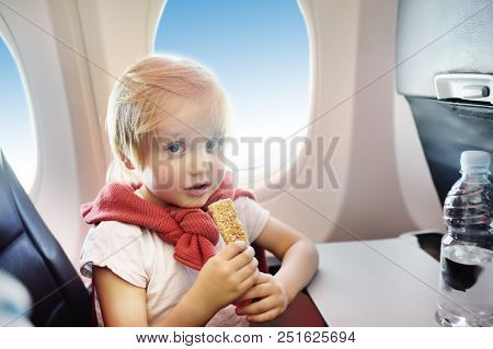 Charming Kid Traveling By An Airplane. Little Boy Drinking Water And Eating Snack During The Flight.