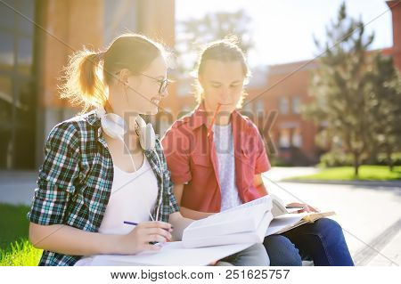 Young Happy Students With Books And Notes Outdoors. Smart Young Guy And Girl In University Campus. L