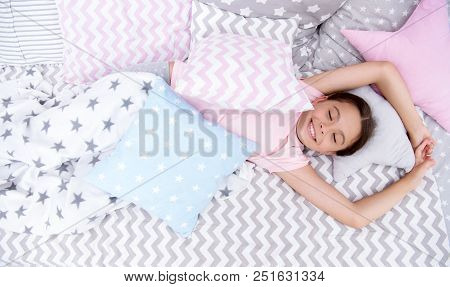 Pleasant awakening. Girl smiling happy child lay on bed with star pattern pillows and cute plaid in her bedroom. Bedclothes for children. Modern fashionable bedclothes. Girl kid waking up in morning. poster