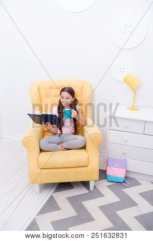 Pleasant evening with book. Girl child sit yellow armchair read book. Kid prepare to go to bed. Pleasant time cozy interior. Girl kid long hair cute pajamas relax and read fairytale book before sleep. poster