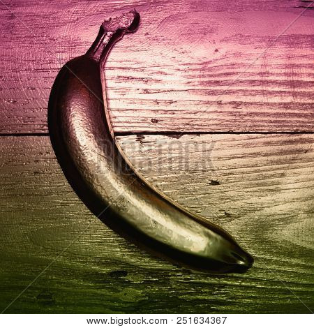 Gold Painted Banana On Golden And Wooden Background. Double Color Filter