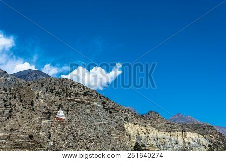 Pyramid And A Small Stupa Against A Rocky Mountain Range, Nepal.