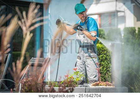 Pressure Washing In The Garden. Caucasian Men In His 30s And The Spring Cleaning.