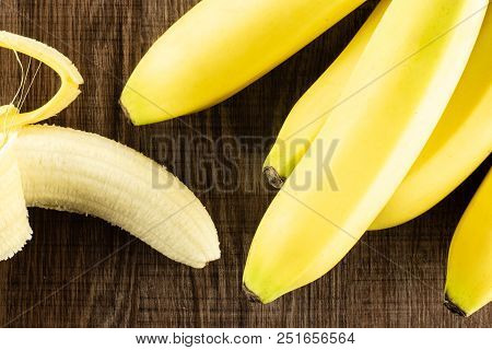 Lot Of Whole Fresh Yellow Banana And One Opened Flatlay On Brown Wood