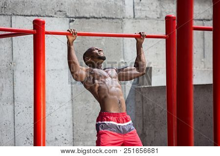 The Fit Athlete Doing Exercises At Stadium. Afro Or African American Man Outdoor At City. Pull Up Sp