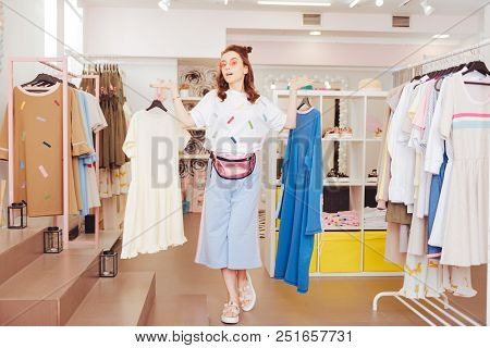 Owner Of Showroom. Young Prosperous Owner Of New Showroom Hanging New Dresses On Clothes Racks