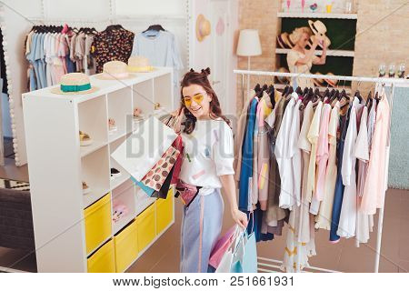 Shoes Stand. Stylish Happy Shopaholic Wearing Bright Clothes Standing Near Shoes Stand In Showroom