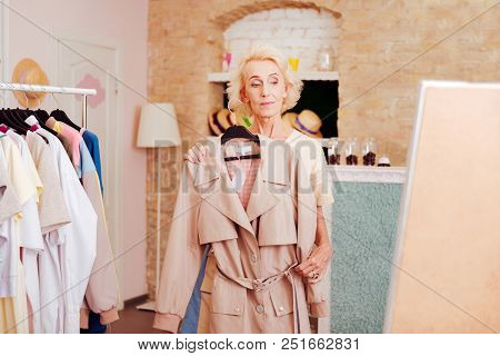 Light Pink Trench. Good-looking Retired Woman Feeling Contended While Buying Light Pink Trench