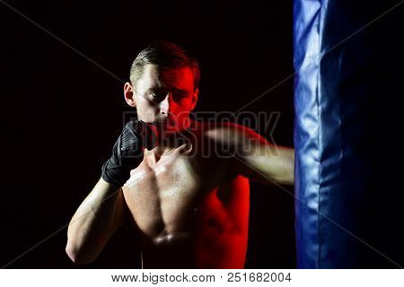 Strength Concept. Sportsman Develop Muscular Strength By Kicking Punching Bag. Man Boxer Do Strength