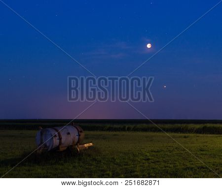 The July 2018 Bloodmoon (lunar eclipse) seen above a meadow on Schiermonnikoog, a dutch Island. You