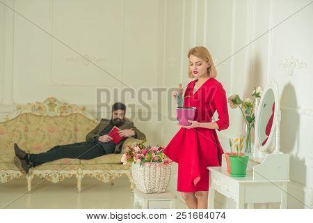 Gardener Concept. Woman And Man On Sofa. Pretty Gardener Take Care Of Plant And Hipster Reading A Bo