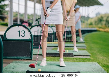 Partial View Of Women With Golf Clubs Playing Golf At Golf Course