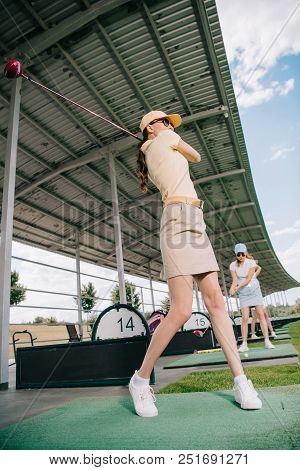 Low Angle View Of Women With Golf Clubs Playing Golf At Golf Course