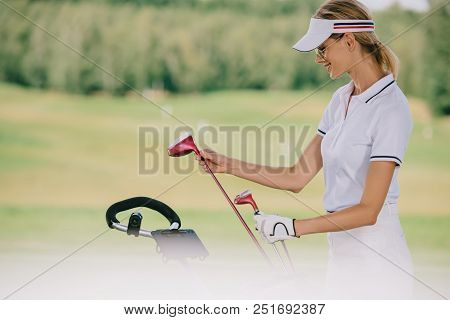 Selective Focus Of Smiling Female Golf Player In Cap With Golf Gear At Golf Course
