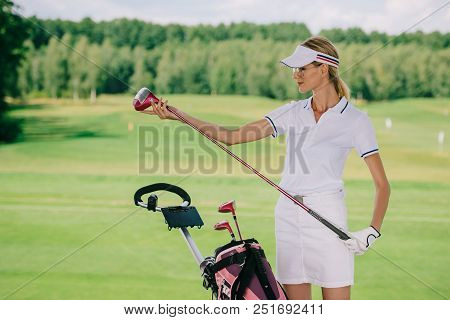 Portrait Of Female Golf Player In Cap With Golf Gear At Golf Course