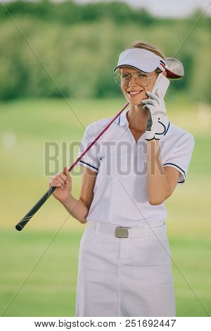 Portrait Of Smiling Female Golf Player In Polo And Cap With Golf Club In Hand Talking On Smartphone