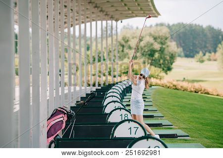 Woman In Polo, Cap And Sunglasses With Golf Club In Hands Playing Golf At Golf Course