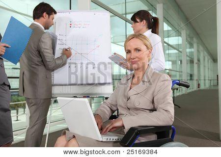 Empresaria sentado en una silla de ruedas durante una presentación