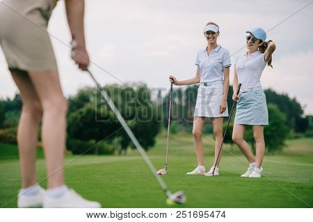 Selective Focus Of Smiling Women In Caps With Golf Equipment Looking At Friend Playing Golf At Golf