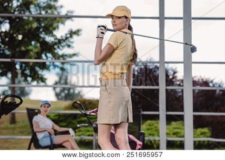 Selective Focus Of Female Golf Player With Golf Club And Friend Resting Behind At Golf Course