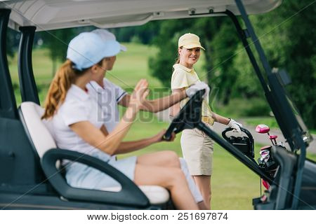 Selective Focus Of Female Golfers In Caps In Golf Cart Greeting Friend With Golf Gear At Golf Course
