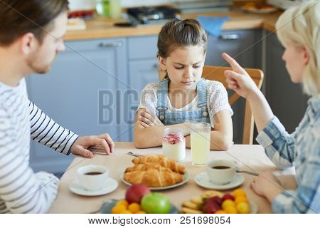 Sad little girl sitting by table while mother forbidding her to have dessert because of bad behavior