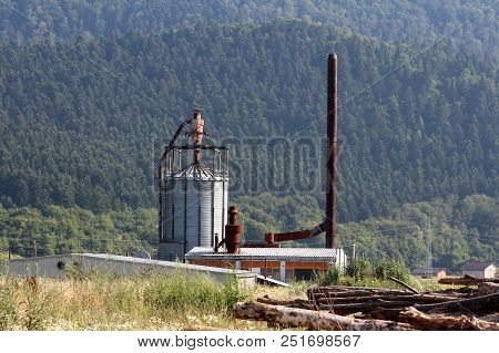 Wood Processing Plant With Tall Rusted Chimney And Storage Silo Behind Tree Logs Surrounded With Tal