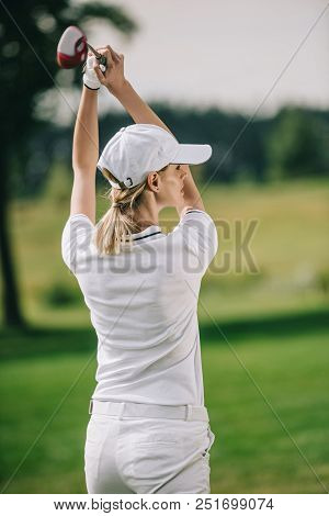 Back View Of Female Golf Player In Cap With Golf Club In Hands At Golf Course