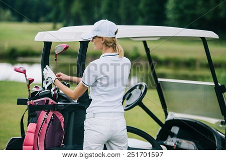 Back View Of Woman In Polo And Cap With Golf Gear Standing At Golf Cart At Golf Course On Summer Day