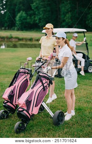 Selective Focus Of Female Golf Players With Golf Equipment And Friend In Golf Cart Behind On Green L