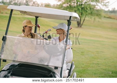 Smiling Female Golf Players Riding Golf Cart At Golf Course