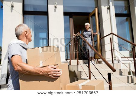 Portrait of modern senior couple unloading cardboard boxes while moving to new house, focus on man in front