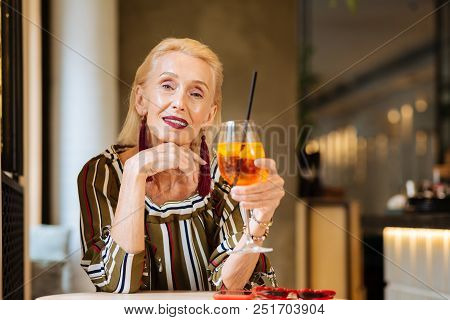 Perfect Rest. Cheerful Nice Woman Smiling To You While Holding A Glass Of Cocktail