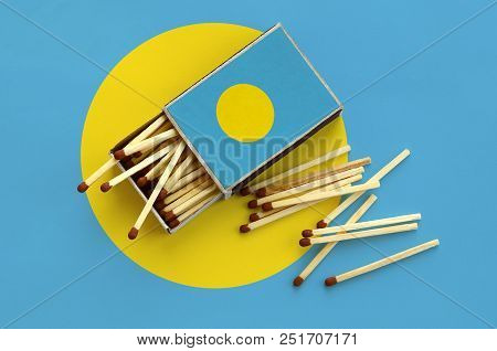 Palau flag  is shown on an open matchbox, from which several matches fall and lies on a large flag. poster