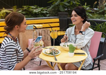 Beaming Woman. Beaming Woman Wearing Striped Dress And Jeans Jacket Sitting In Cafe With Her Sister