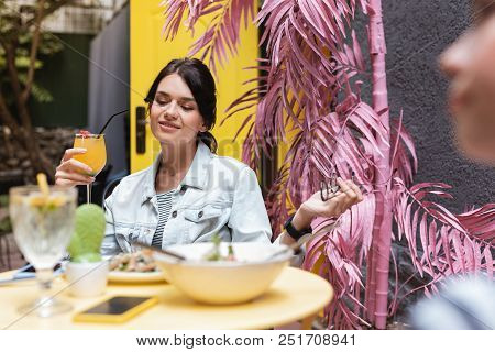 Relaxing On Terrace. Stylish Dark-haired Woman Relaxing On Decorated Summer Terrace With Her Best Fr