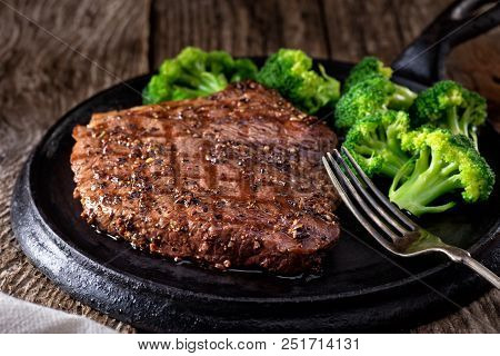 A Delicious Grilled Pepper Steak With Broccoli On A Rustic Wooden Table.