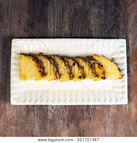 Pineapple Fruit Cut In Wedges On Plate Wooden Background Healthy Snack.
