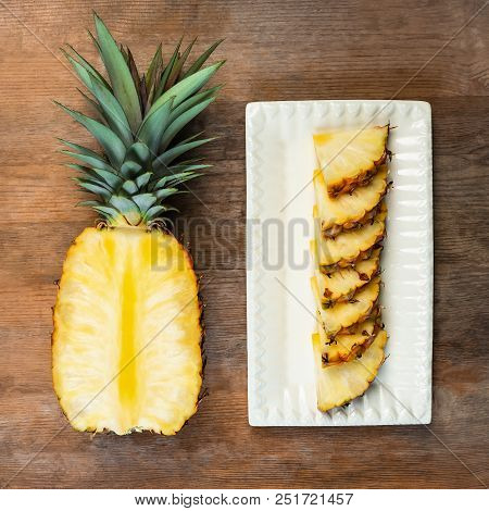 Pineapple Fruit Cut Half And Wedges And  Displayed On White Plate And Wooden Background. Square Comp