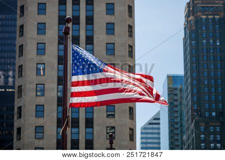 Close Up Of Waving Flag Of The United States In Downtown Chicago With High Buildings In The Backgrou