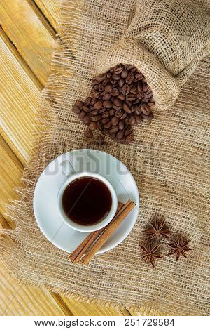 A Coffee Cup With Cinnamon And Badyan On A Saucer And Coffee Beans In A Sack On A Wooden Table