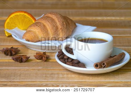 Cup Of Coffee, Cinnamon, Illicium And Croissant On A Wooden Background