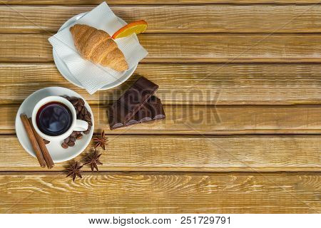 Coffee On White Saucer, Cinnamon And Croissant With Chocolate On A Wooden Background, Top View. Copy