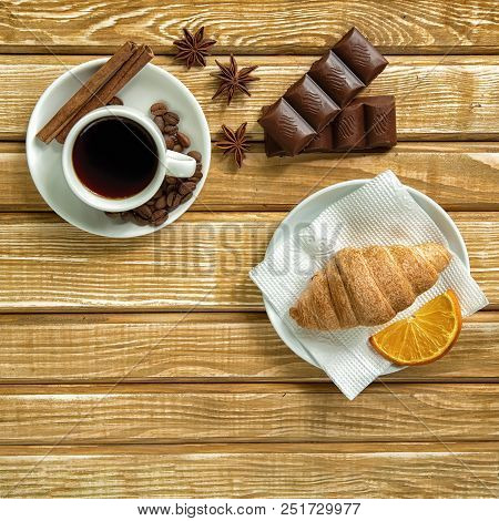 Coffee On White Saucer, Cinnamon And Croissant With Chocolate On A Wooden Background, Top View.