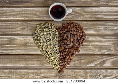 Heart Of Fried And Green Coffee Beans, A Cup Of Coffee On Wooden Background.