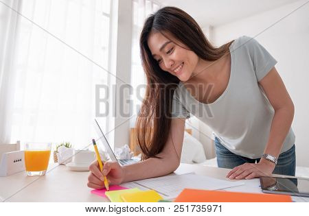 Asian Female Freelancer Standing And Writing On Paperwork Working On Table In Bedroom At Home.work A