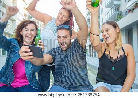 Group Of Smiling Friends Watch The Tablet And Exult